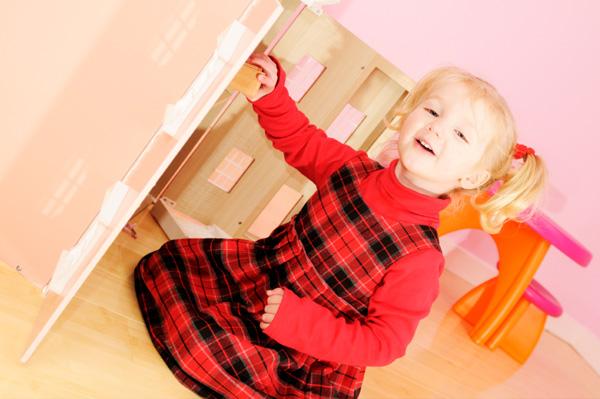 Preschooler putting away her toys