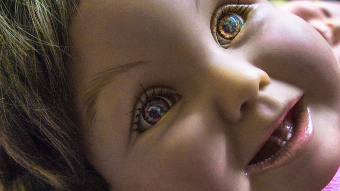 Realistic toy doll's face smiling at