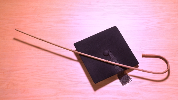 Mortarboard and cane and punishment