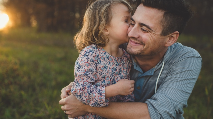 Girl kissing father on cheek in