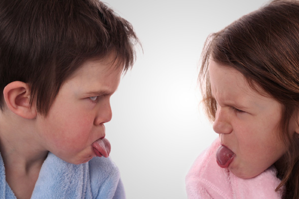 Siblings sticking out tongue at each other
