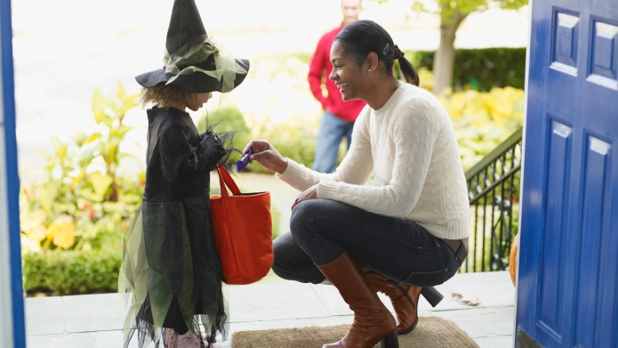 African woman giving candy to trick