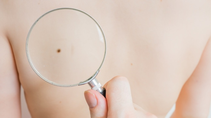 Doctor holds magnifying glass in hand