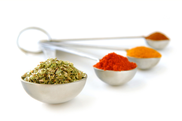 Assorted spices in metal measuring spoons