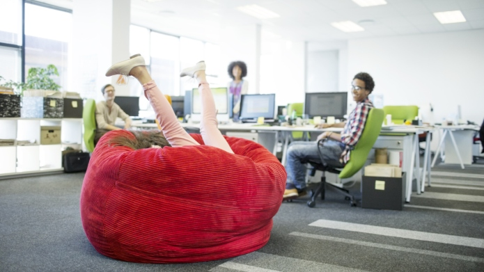 Businesswoman playing in beanbag chair in
