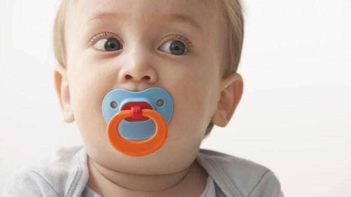 Mixed race baby boy sucking pacifier