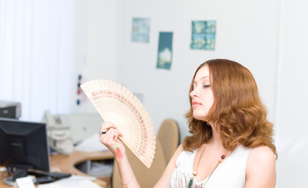 woman fanning herself in a hot room