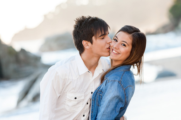 Teen couple on beach in intimate embrace