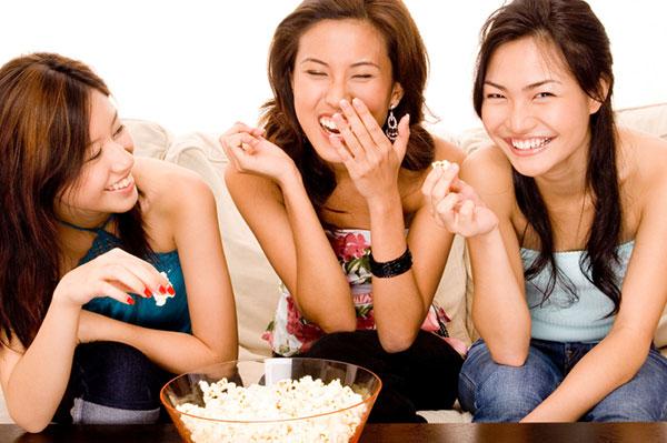 Three friends eating popcorn and having fun | Sheknows.ca