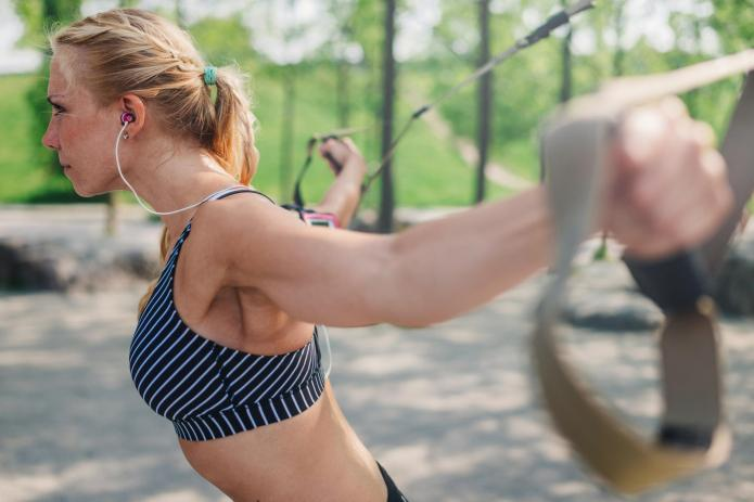 Woman doing suspension workout outdoor.