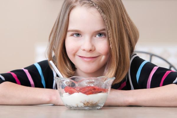 Tween girl eating yogurt
