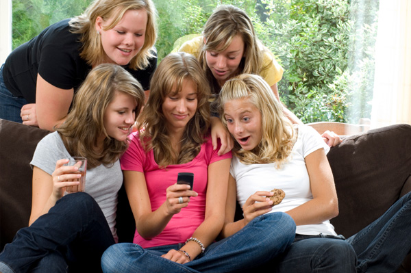 Tweens looking at cell phone