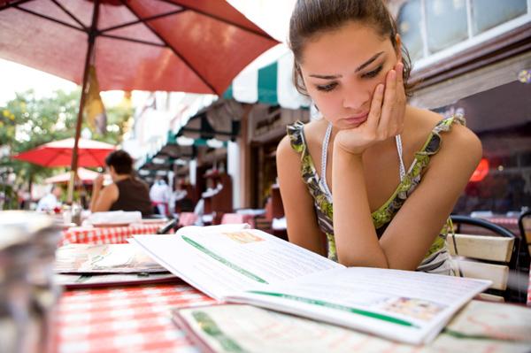 Unhappy woman looking at menu