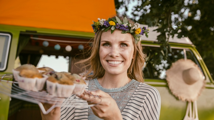 Hippie woman presenting vegan muffins in