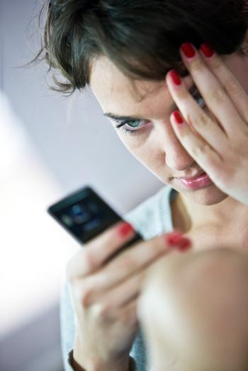 Upset woman reading text message