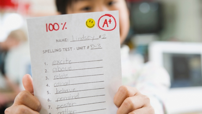 Elementary student holding an A grade