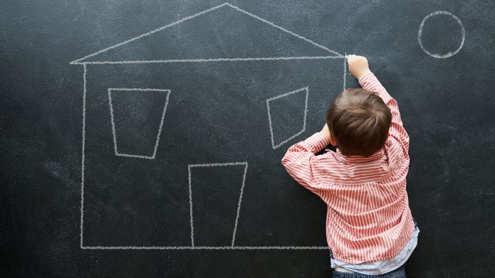 A little boy drawing a house