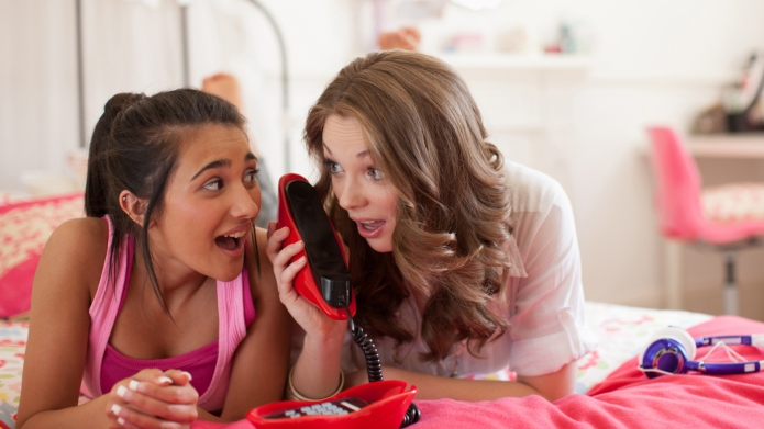 Teenage girls talking on telephone in