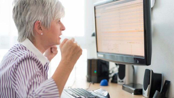 Senior woman looking horrified at computer