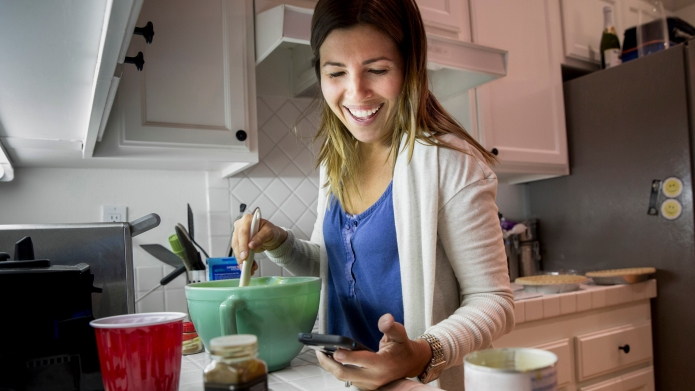 Woman preparing food in kitchen whilst