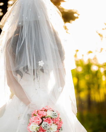 Holding pink flowers in wedding dress outside