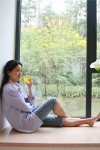 woman sitting on window seat with drink