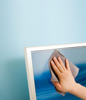 Woman wiping computer screen