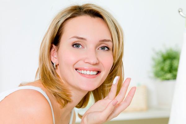 Woman applying anti-agin lotion