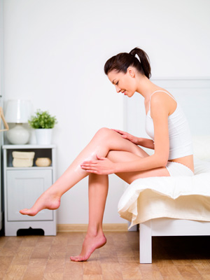 woman sitting on bed applying lotion