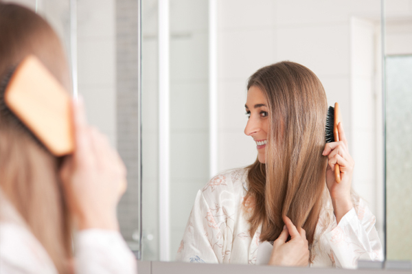 Woman brushing her hair in the mirror