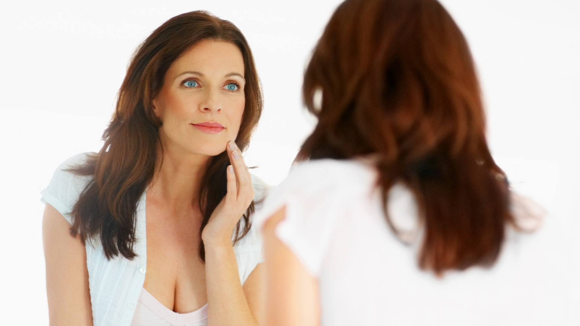 Woman checking skin in mirror | Sheknows.com