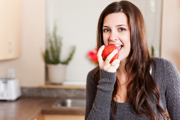 Woman eating apple at home