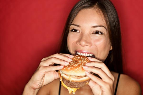 Woman eating fast food burger