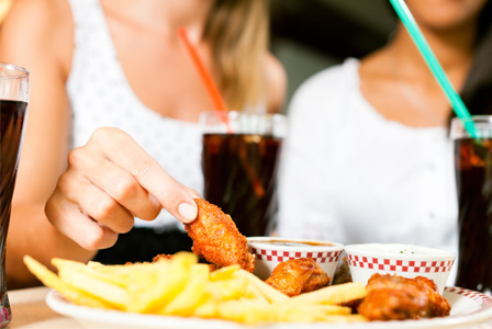 Woman eating fried food and drinking soda