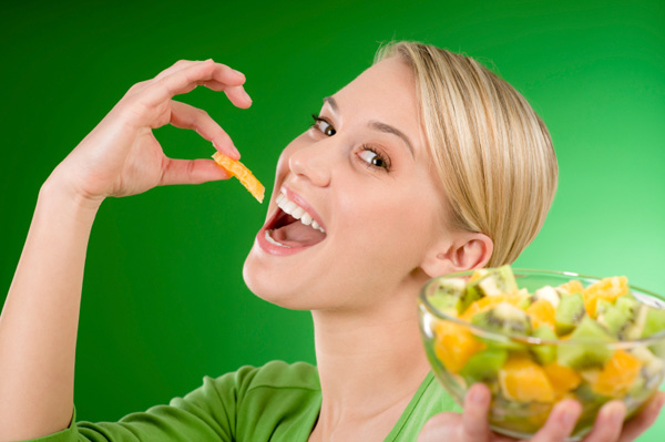 Woman eating oranges and kiwi
