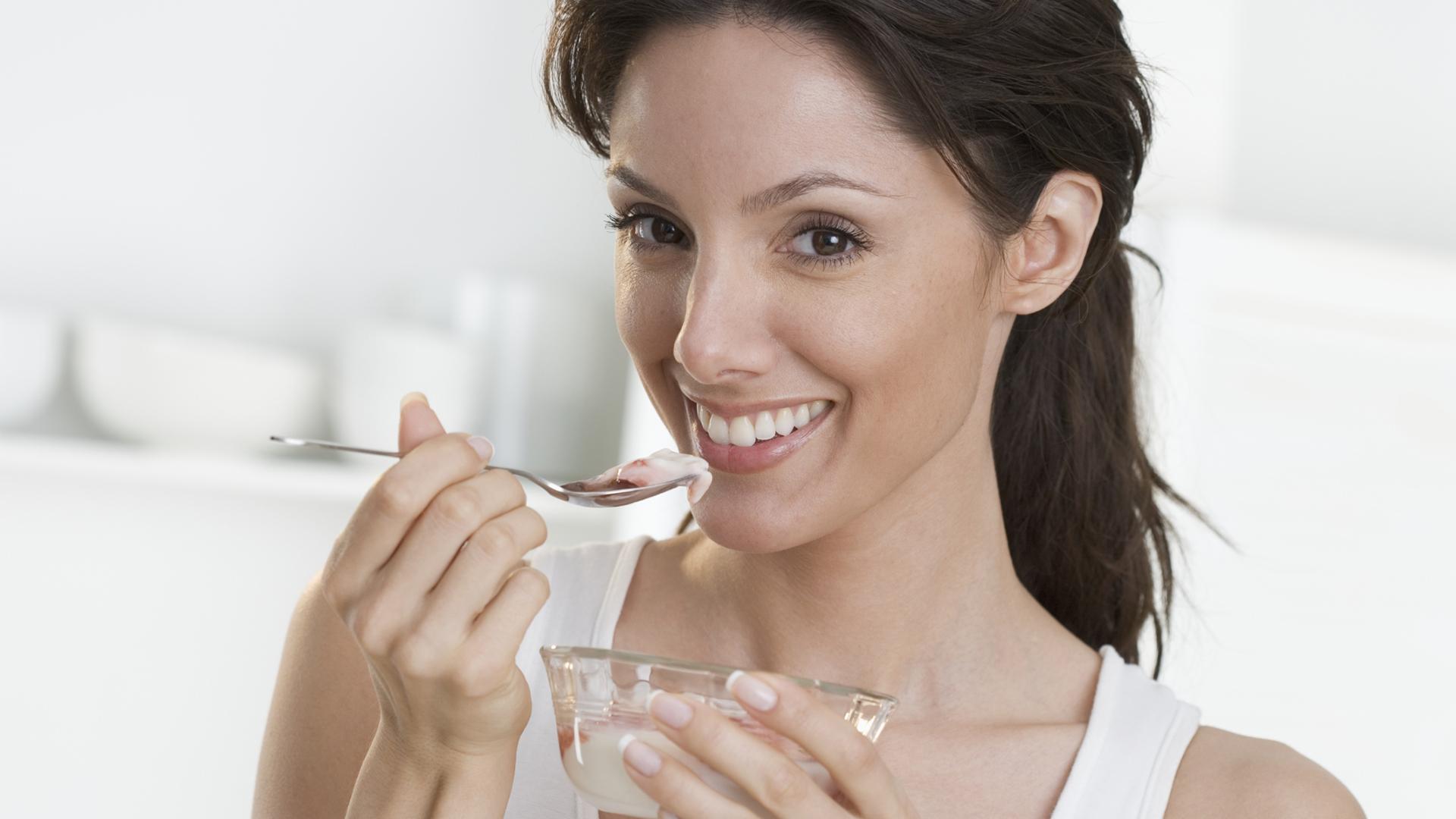 Woman eating yogurt | SheKnows.com