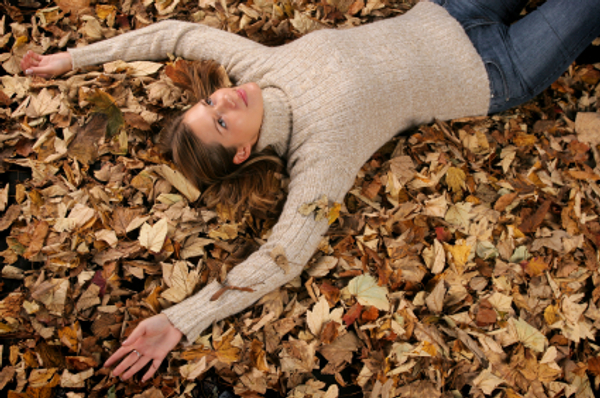 Woman laying in fall leaves