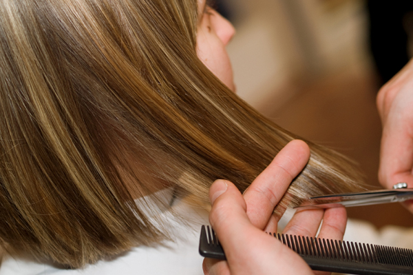 Woman getting hair trimmed