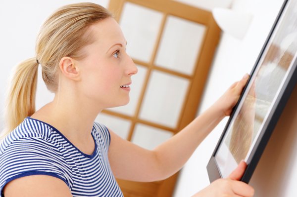 woman personalizing her decor by hanging picture frame