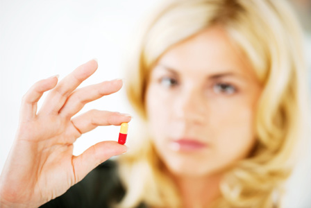 Woman holding diet pill