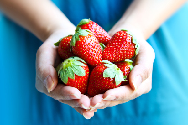 Woman holding fresh strawberries