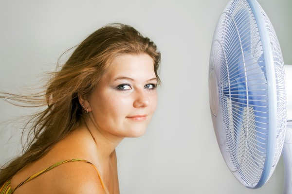 woman sitting in front of fan cooling off