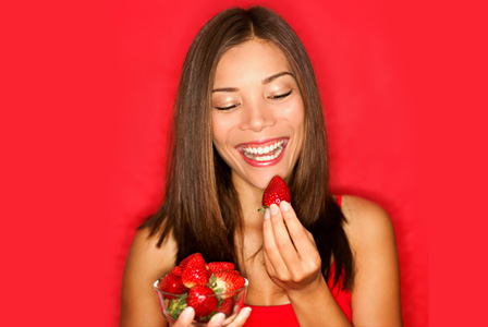 Woman in red eating strawberry
