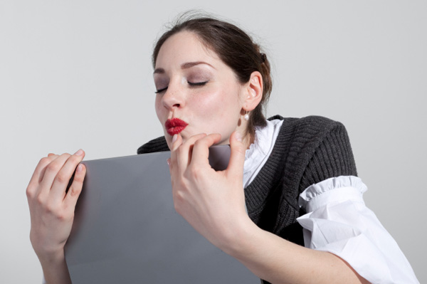 Woman kissing computer