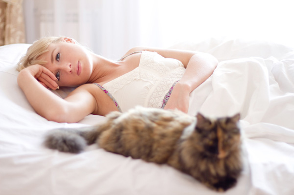 Woman laying in bed with cat