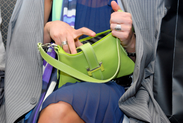 Woman looking inside leather handbag