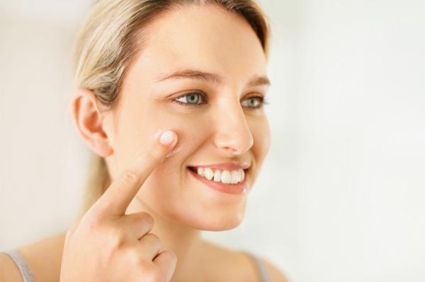 Woman moisturizing face