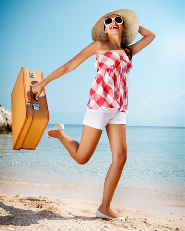 Woman on beach with suitcase