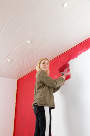 Woman painting accent wall red