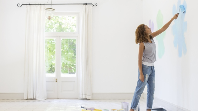 Woman painting wall in living space